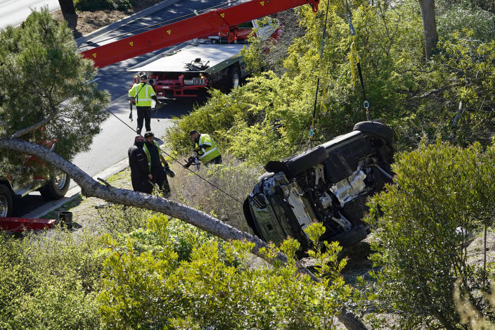 """FILE - In this Feb. 23, 2021, file photo, a vehicle rests on its side after a rollover accident involving golfer Tiger Woods in the Rancho Palos Verdes suburb of Los Angeles. Detectives are looking at data from the so-called """"black box"""" of Tiger Woods' SUV to get a clearer picture of what occurred during the Southern California rollover crash last week that seriously injured the golf star, authorities said Wednesday, March 3. (AP Photo/Marcio Jose Sanchez, File)"""