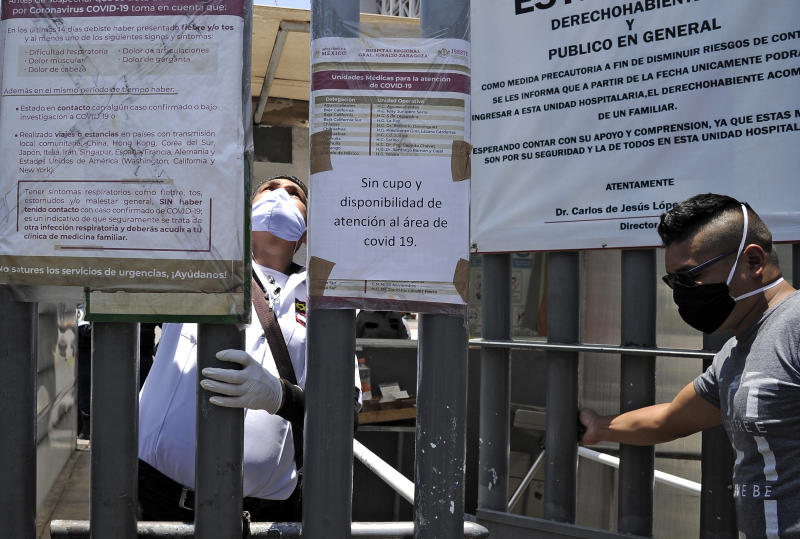 Employees are seen at the entrance of the Zaragoza Hospital, where a sign reads No place or availability for assistance at the COVID-19 area, in Mexico City on May 06, 2020. - The desperate search for hospitals and the lack of medical reports deepens the distress of relatives of COVID-19 patients in Mexico. (Photo by CLAUDIO CRUZ / AFP) (Photo by CLAUDIO CRUZ/AFP via Getty Images)