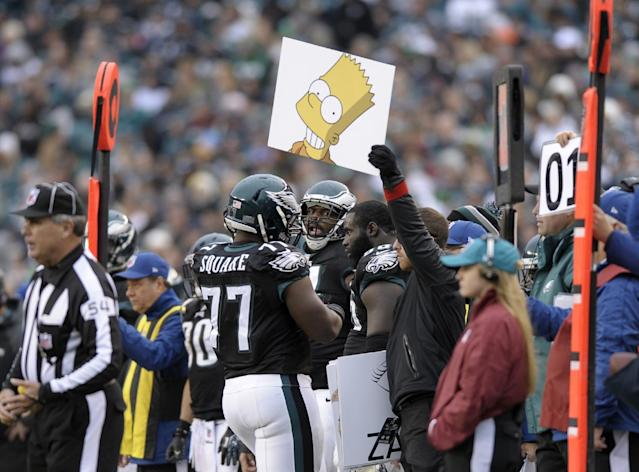 FILE - In this Dec. 1, 2013 file photo, Philadelphia Eagles sports science coordinator Shaun Huls holds a placard, center, during the second half of an NFL football game against the Arizona Cardinals, in Philadelphia. Eagles rookie head coach Chip Kelly finds signs better for communicating then microphones because the whole team can see the information and speed up his lightning-fast offense. (AP Photo/Michael Perez, File)