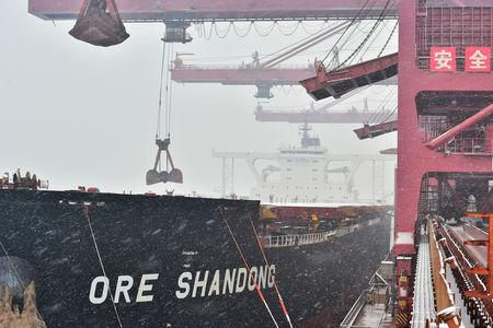 Cranes unload imported iron ore from a ship amid snow at the iron ore terminal of Qingdao port