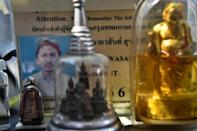 Wasan's official taxi identification card behind some of his protective Buddhist figurines