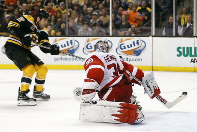 Boston Bruins' Milan Lucic, left, scores on Detroit Red Wings goalie Jimmy Howard during the second period of Game 2 of a first-round NHL hockey playoff series in Boston Sunday, April 20, 2014