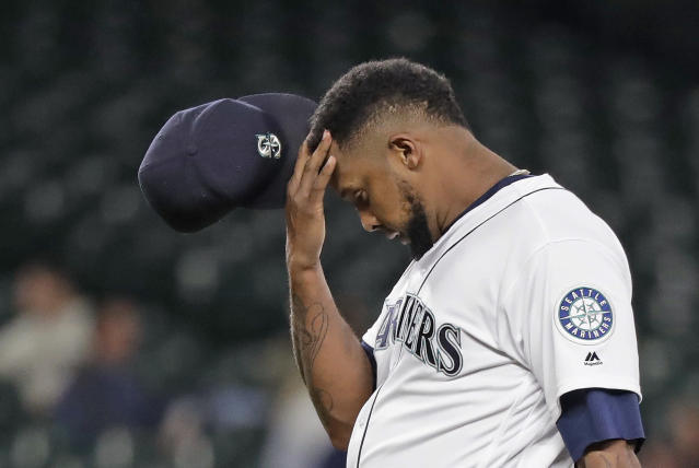 Seattle Mariners relief pitcher Juan Nicasio rubs his head after giving up a two-run home run to the Oakland Athletics during the eighth inning of a baseball game Wednesday, May 2, 2018, in Seattle. (AP Photo/Elaine Thompson)