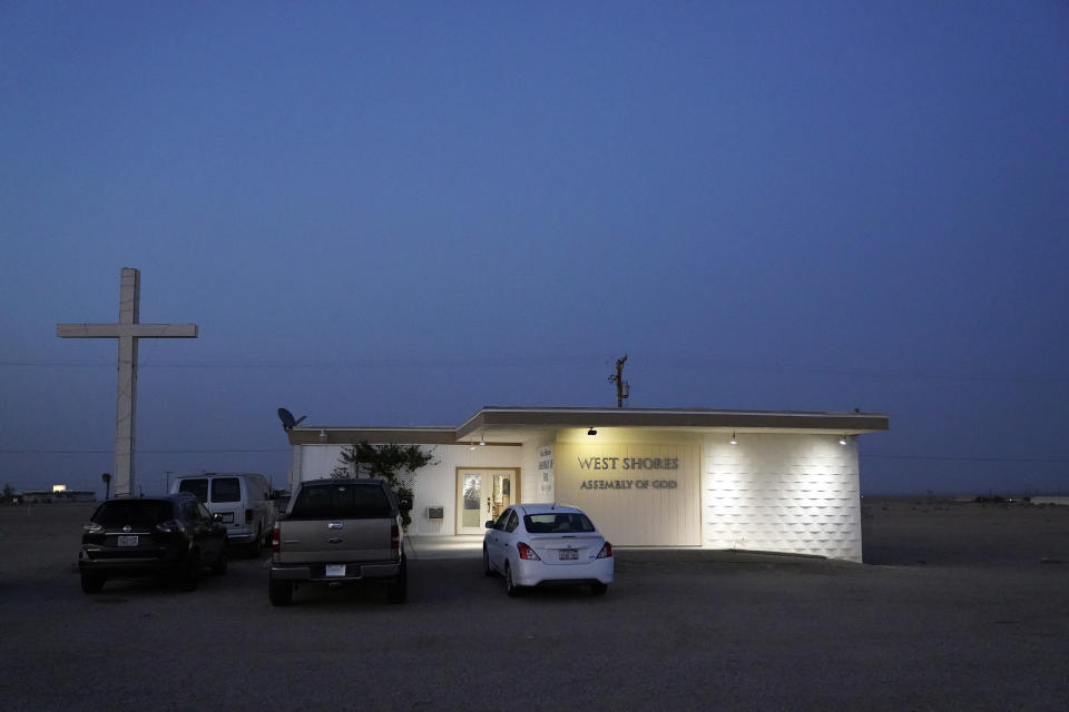 The West Shores Assembly of God building is lit up at dusk Wednesday, July 14, 2021, in Salton City, Calif. The community on the shore of the Salton Sea, California's largest but rapidly shrinking lake, has been through decades of economic stagnation. Now, it's at the forefront of efforts to make the U.S. a major global producer of lithium, the ultralight metal used in rechargeable batteries. (AP Photo/Marcio Jose Sanchez)