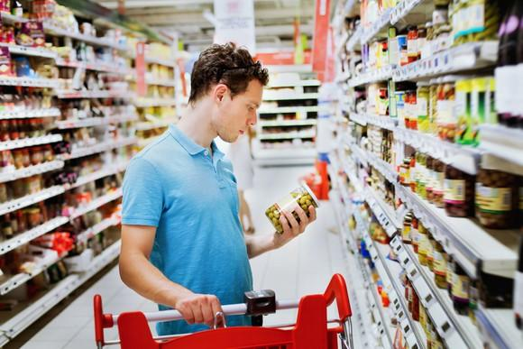 A man with a shopping cart in a grocery aisle, inspecting a jar of olives