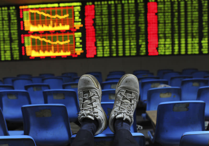 An investor puts his feet onto the back of a chairs in front of an electronic board displaying stock information at a brokerage house in Hefei