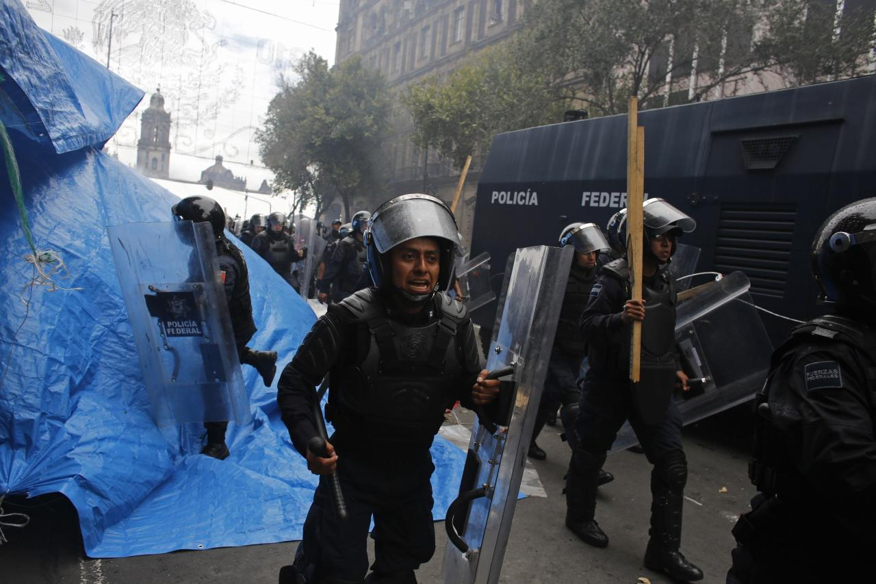 Riot policemen charge towards protesters in downtown Mexico City September 13, 2013. Police used tear gas and water cannons to disperse demonstrators in the main square of Mexico City on Friday, arresting 31 people, as the government took control of the historic center after weeks of protests by teachers. Federal police clashed with some protestors as they cleared the massive square, or Zocalo, for celebrations on Sunday, when President Enrique Pena Nieto is due to lead his first traditional remembrance of the heroes of Mexican independence. REUTERS/Tomas Bravo (MEXICO - Tags: CIVIL UNREST POLITICS EDUCATION BUSINESS EMPLOYMENT)