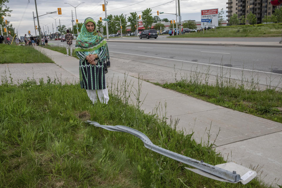 Torpenky Khan, a Muslim, looks at a street sign that was destroyed during the attack.