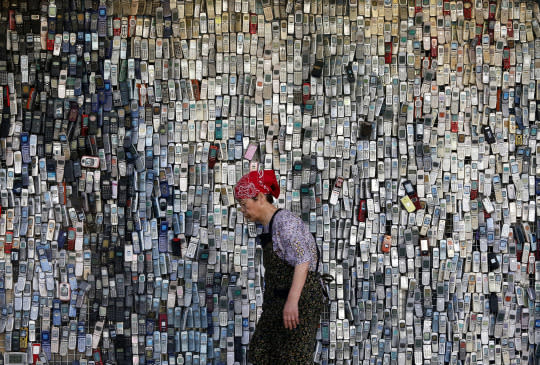 <p>A woman walks past a wall of mock-up mobile phones displayed outside an electronics store in downtown Tokyo, Japan, June 2, 2016. The store owner started this display with a few thousands of cellphones ten years ago, which continue to draw attention from those who pass by. (Shuji Kajiyama/AP) </p>