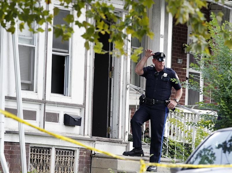 """A police officer stands at the doorway of 1415 Kaighn Ave., in Camden, N.J., Wednesday, Aug. 22, 2012, after police in Camden say a 2-year-old boy was decapitated, apparently by his mother, and his head left in the freezer of their home before woman fatally stabbed herself. Chevonne Thomas, 33, called 911 just after midnight to say something had happened to her child and it """"sounded like she had done it,"""" Camden County Prosecutor's Office spokesman Jason Laughlin said. Officers found Zahree Thomas' body on the first floor of the home and the boy's head in the freezer. (Photo/Mel Evans)"""