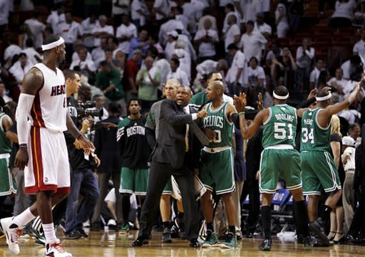Boston Celtics head coach Doc Rivers, center, celebrates with Ray Allen (20), Keyon Dooling (51) and Paul Pierce (34) as Miami Heat's LeBron James, left, walks past during the second half of Game 5 in their NBA basketball Eastern Conference Finals playoff series, Tuesday, June 5, 2012, in Miami. The Celtics won 94-90. (AP Photo/Lynne Sladky)