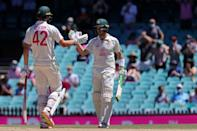 Cameron Green (left) is congratulated by captain Tim Paine after making his maiden Test half-century on the fourth day in Sydney