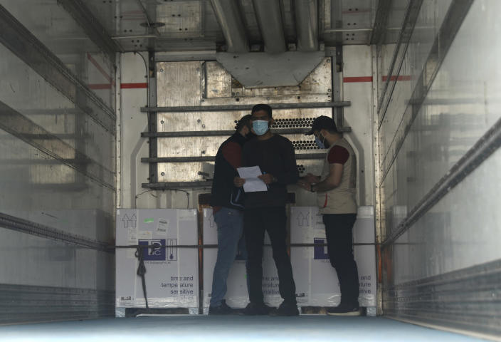 Heath workers check boxes of AstraZeneca COVID-19 vaccines inside a truck, that were delivered to Idlib through a border crossing with Turkey, in Bab Al-Hawa, northwestern Syria, Wednesday, April 21, 2021. Syria's last rebel-held enclave received its first batch of COVID-19 vaccines on Wednesday, with a refrigerated truck offloading over 50,000 of United Nations-secured jabs in the overcrowded province. (AP Photo/Ghaith Alsayed)