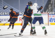 Edmonton Oilers' Alex Chiasson (39) and Vancouver Canucks' Travis Hamonic (27) fight during second-period NHL hockey game action in Edmonton, Alberta, Thursday, May 6, 2021.. (Jason Franson/The Canadian Press via AP)