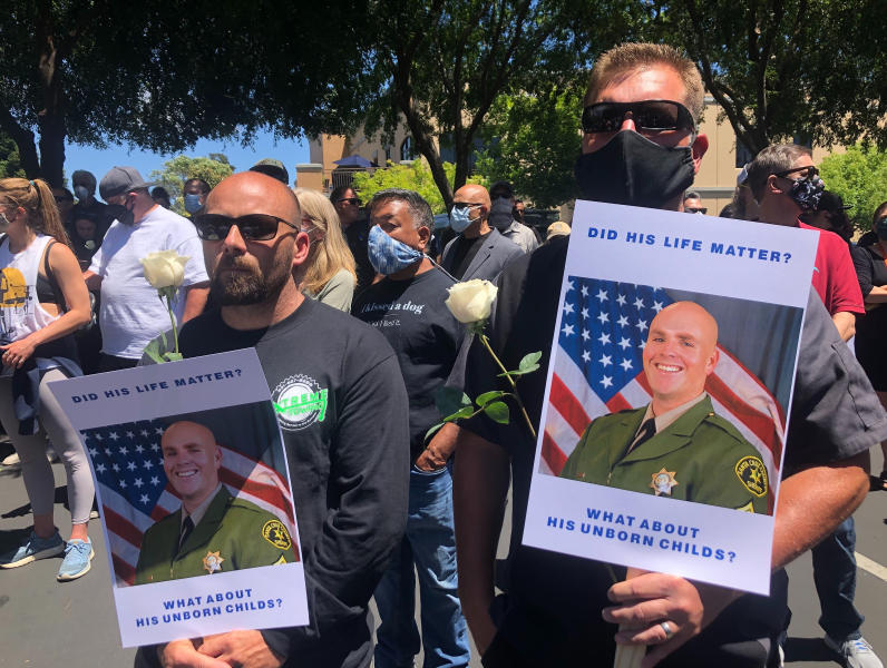 Matthew Rose, left, and Michael Carr, of Santa Cruz County hold posters of slain Sgt. Damon Gutzwiller, as they join others outside the Santa Cruz County Sheriff-Coroner's Office to pay their respects in Santa Cruz, Calif., Sunday, June 7, 2020. Santa Cruz County Sheriff's Sgt. Gutzwiller, 38, was shot and killed in Ben Lomond, an unincorporated area near Santa Cruz. Sheriff Jim Hart said the suspect, Steven Carrillo, was shot during the arrest and is being treated at a hospital. (AP Photo/Martha Mendoza)