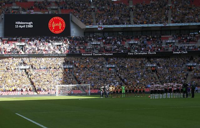 Hull City's players, left, and Sheffield United's players observe a minute silence in memory of the victims of Hillsborough before the start of their English FA Cup semifinal soccer match at Wembley Stadium in London, Sunday, April 13, 2014. 96 soccer supporters died and many injured at the Hillsborough Stadium in Sheffield on April 15, 1989, during the FA Cup semifinal soccer match between Liverpool and Nottingham Forest. (AP Photo/Sang Tan)