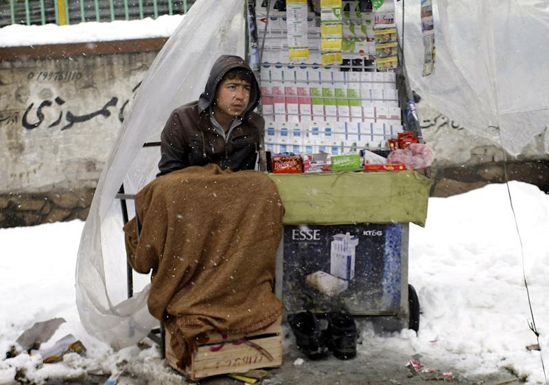 An Afghan boy waits for customers to buy cigarettes, sweets and mobile phone credit cards during a snowstorm in Kabul, Afghanistan, Monday, Feb. 4, 2013. Kabul has been experiencing below freezing weather and snow for several days. (AP Photo/Musadeq Sadeq)
