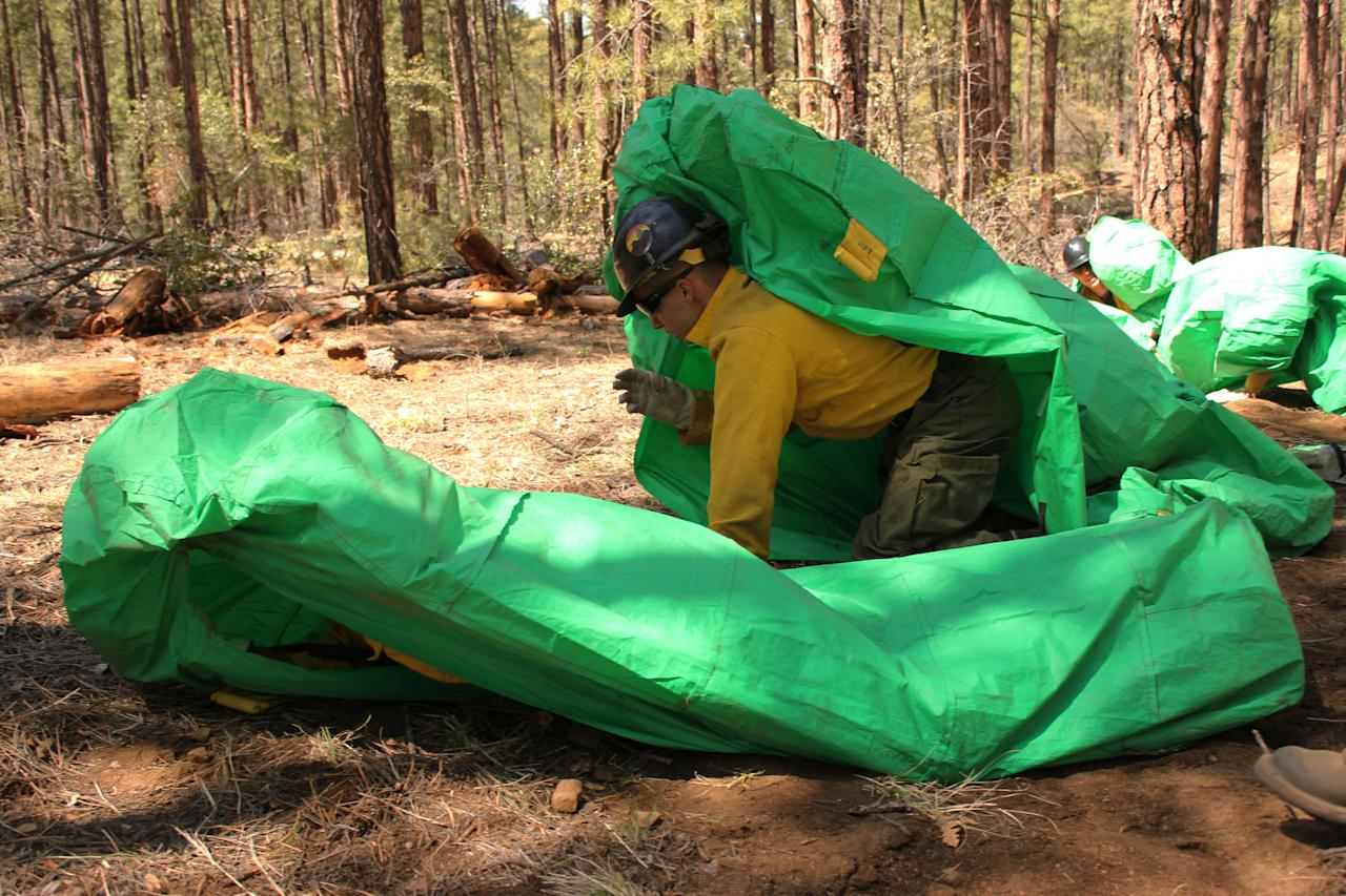 ADDS IDENTIFICATION - In this April 12, 2012 photo provided by the Cronkite News, Granite Mountain Hotshots crew member Shane Arollado trains with others on setting up emergency fire shelters outside of Prescott, Ariz. On Sunday, June 30, 2013, 19 members of the Prescott-based crew were killed in the deadliest wildfire involving firefighters in the U.S. for at least 30 years. The firefighters were forced to deploy their emergency fire shelters - tent-like structures meant to shield firefighters from flames and heat - when they were caught near the central Arizona town of Yarnell, according to a state forestry spokesman. (AP Photo/Cronkite News, Connor Radnovich)