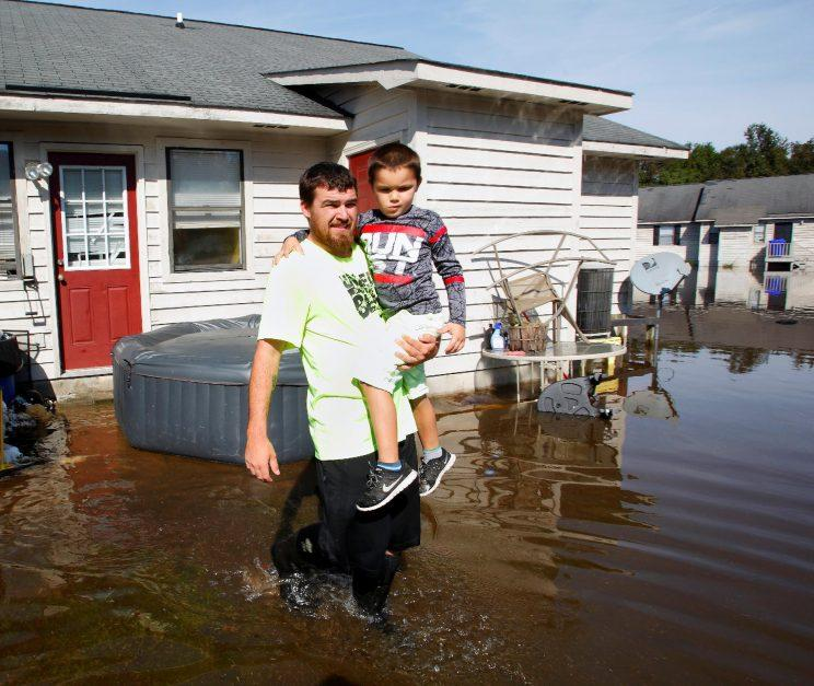 A man carries his son through flood waters surrounding their home after inspecting it amidst rising river levels in the aftermath of Hurricane Matthew, in Greenville, N.C. on Oct. 14, 2016. (Photo: Jonathan Drake/Reuters)