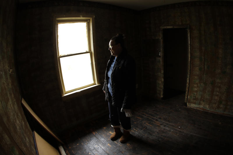 In this photo taken Monday, Nov. 18, 2019, Tammy Kilgore walks through her home for the final time before it was demolished as part of a voluntary buyout in flood-prone Mosby, Mo. Kilgore accepted a $45,000 payment to leave her home of 38 years and has moved to a nearby community. (AP Photo/Charlie Riedel)