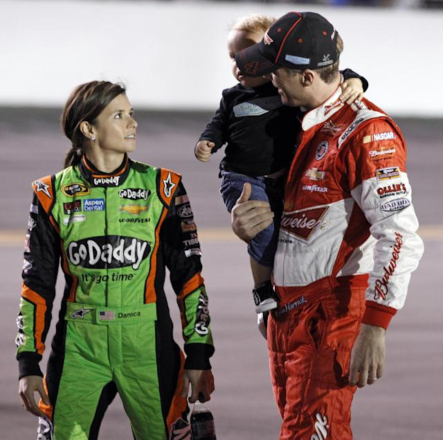 Danica Patrick, left, talks with Kevin Harvick before the first of two NASCAR Sprint Cup series qualifying auto races in Daytona Beach, Fla., Thursday, Feb. 20, 2014. (AP Photo/Terry Renna)