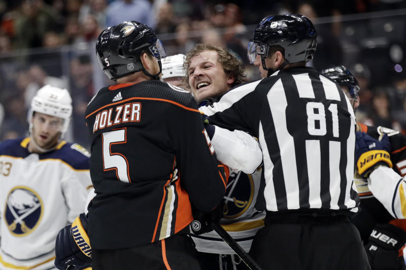 Buffalo Sabres' Jake McCabe, center, gets into a shoving match with Anaheim Ducks' Korbinian Holzer (5) during the second period of an NHL hockey game Wednesday, Oct. 16, 2019, in Anaheim, Calif. (AP Photo/Marcio Jose Sanchez)
