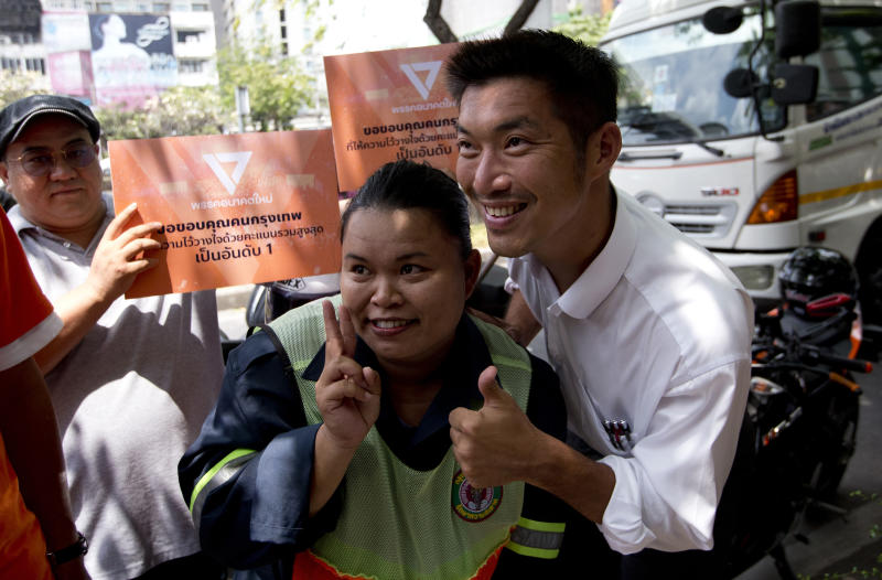 Thailand's Future Forward Party leader Thanathorn Juangroongruangkit, right takes a picture with a supporter before on vehicle to thank people who came out to vote Bangkok, Thailand, Wednesday, April 3, 2019. Thailand's ruling junta has filed a complaint accusing Thanathorn of sedition and aiding criminals. The Future Forward Party ran a strong third in the elections last month that were also contested by a pro-military party. (AP Photo/Sakchai Lalit)