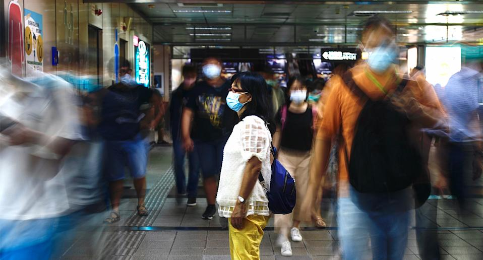A lady wears a surgical mask in a busy underground station.