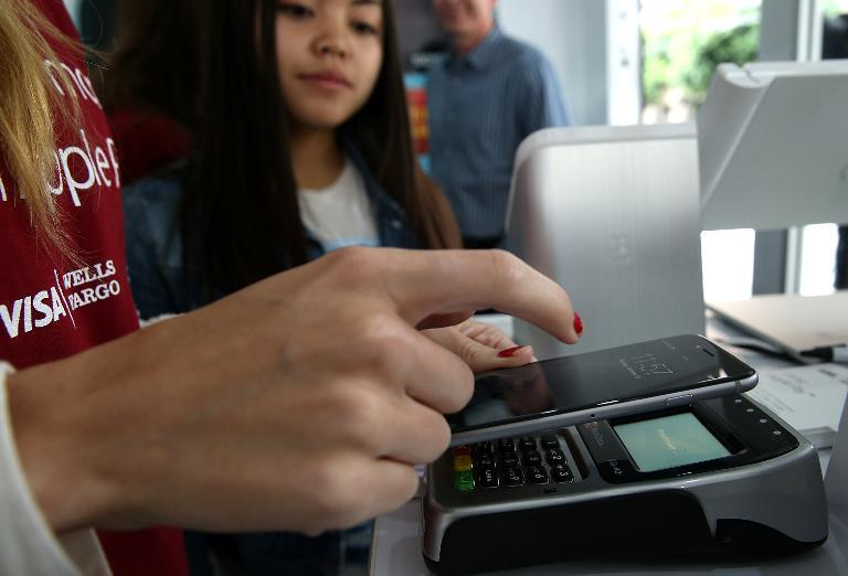 A worker demonstrates Apple Pay inside a mobile kiosk sponsored by Visa and Wells Fargo to demonstrate the new Apple Pay mobile payment system on October 20, 2014 in San Francisco