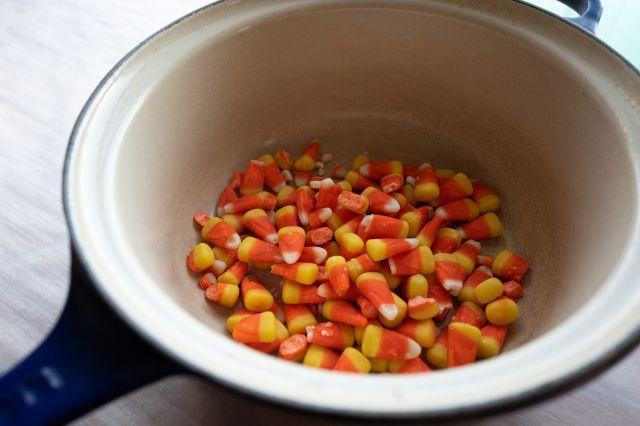 A photo of candy corn in the bottom of an enameled sauce pan.