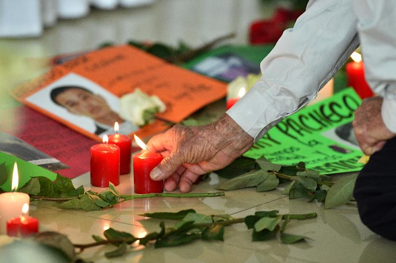 A relative of a victim of the armed conflict in Colombia lights a candle during a ceremony marking the dignified return of the remains, in Villavicencio on December 17, 2015 (AFP Photo/Guillermo Legaria)