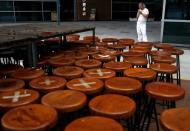 Kitchen assistant takes a break next to an outdoor seating area of a closed restaurant in Singapore