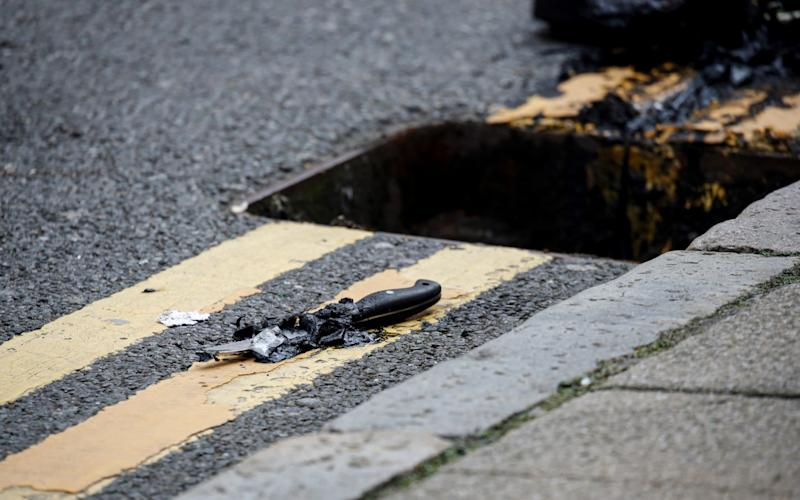 A knife lies on the pavement after being recovered by the police from a drain following reported stabbings in Birmingham - REUTERS/Phil Noble