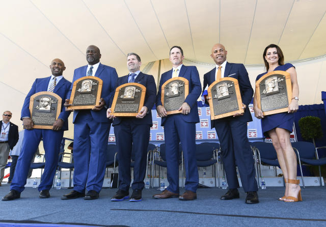 National Baseball Hall of Fame inductees Harold Baines, Lee Smith, Edgar Martinez, Mike Mussina, Mariano Rivera , and Brandy Halladay window of the late Roy Halladay hold their plaques for photos after the induction ceremony at Clark Sports Center on Sunday, July 21, 2019, in Cooperstown, N.Y. (AP Photo/Hans Pennink)
