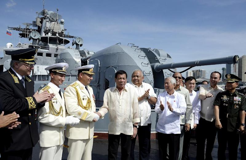FILE - In this Jan. 6, 2017, file photo, Philippine President Rodrigo Duterte, fourth from left, shakes hands with Russia's Rear Adm. Eduard Mikhailov, third from left, at the anti-submarine navy ship Admiral Tributs at the south pier in Manila, Philippines. A flurry of goodwill visits by ships and submarines has marked the new year in the South China Sea. In the Philippines, two Russian warships docked in Manila for a five-day visit in a showcase by Moscow to demonstrate what it can offer to a traditional U.S. ally. (Noel Celis/Pool Photo via AP, File)