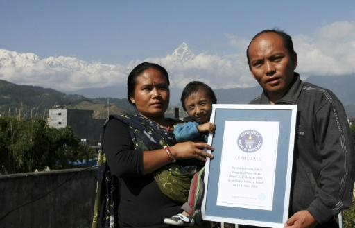 Khagendra Thapa Magar poses with his parents while holding his Guiness World Records certificate at their home in Pokhara in October 2010