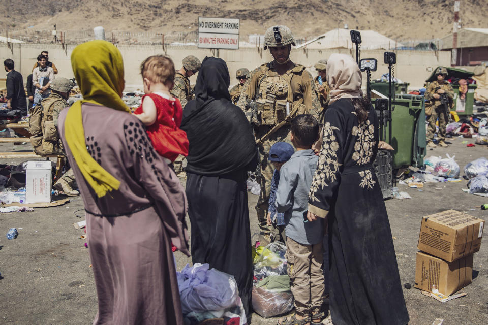 In this image provided by the U.S. Marine Corps, Marines with the 24th Marine Expeditionary Unit process evacuees as they go through the evacuation control center at Hamid Karzai International Airport in Kabul, Afghanistan, Saturday, Aug. 28, 2021. (Staff Sgt. Victor Mancilla/U.S. Marine Corps via AP)
