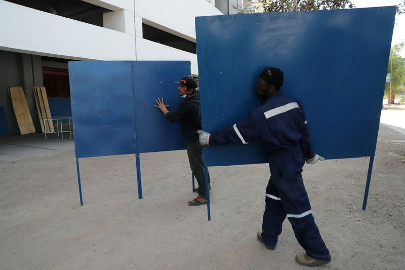 Workers carry sections of voting booths inside a polling station ahead of the upcoming referendum on a new Chilean constitution in Santiago,