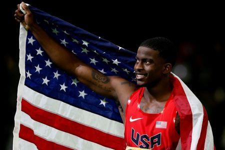 FILE PHOTO: Trayvon Bromell of the U.S. celebrates with an American flag after winning the gold medal in the men's 60 meters at the IAAF World Indoor Athletics Championships in Portland, Oregon, U.S, March 18, 2016. REUTERS/Lucy Nicholson/File Photo