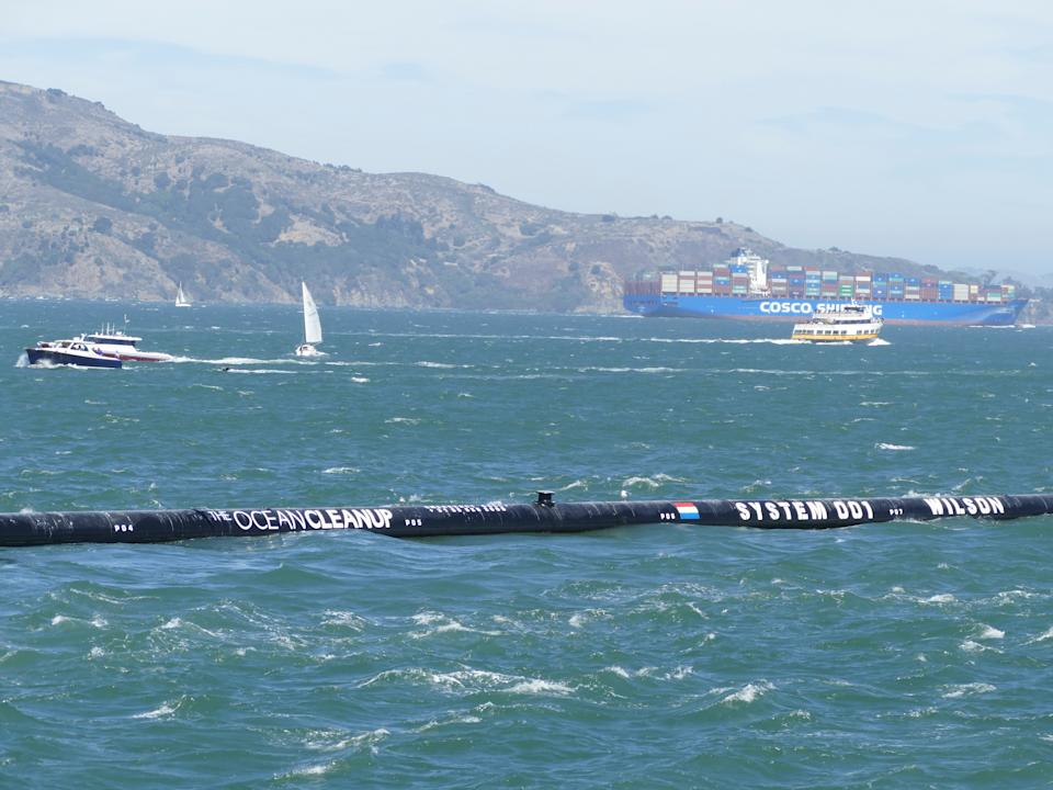 """08.09.2018,USA, San Francisco: The first floating waste collector """"The Ocean Cleanup"""" can be seen on its way to the Pacific Ocean in the bay of San Francisco. Like tentacles, the ends of the 600-meter long plastic pipe of the cleaning system are to lie around mountains of plastic waste - initially on the Pacific between California and Hawaii. Photo: Barbara Munker/dpa (Photo by Barbara Munker/picture alliance via Getty Images)"""