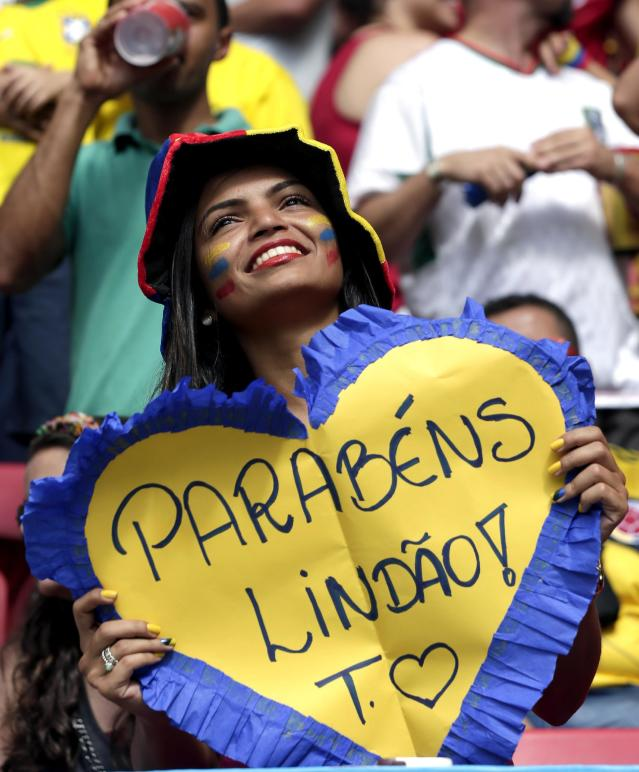 A Colombian supporter holds a sign saying 'Congratulations Handsome' before the group C World Cup soccer match between Colombia and Ivory Coast at the Estadio Nacional in Brasilia, Brazil, Thursday, June 19, 2014. (AP Photo/Marcio Jose Sanchez)