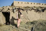 Farmer Atta Jan, 28, shows a wall hit by bullets at his house in Kandahar province