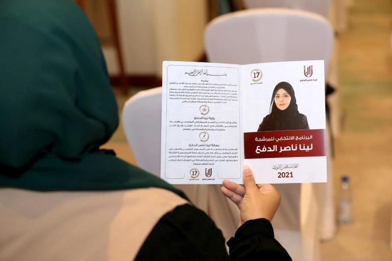 A woman holds a leaflet for the candidate for Qatar's Shura council elections Leena al-Dafa during a campaign event in Doha ahead of the country's first legislative polls (AFP/-)