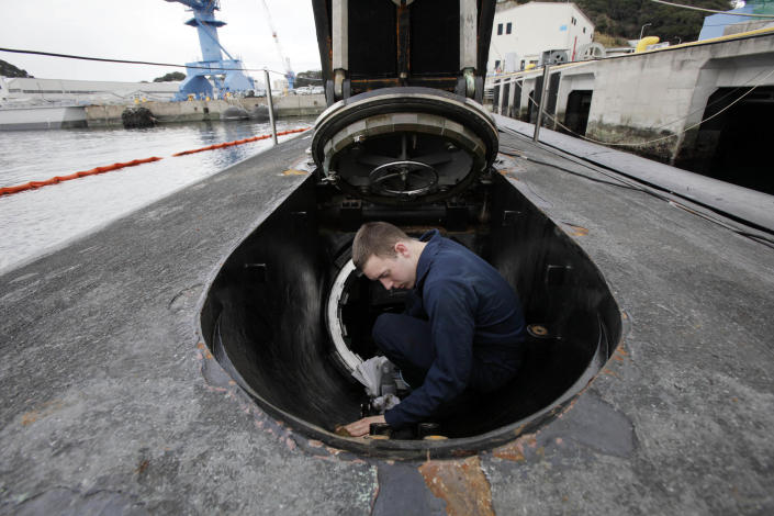 In this Monday, March 12, 2012 photo, Sonar Technician James Corriveau, of Boston, Mass., cleans the weapons shipping hatch on the USS Connecticut, a Sea Wolf-class nuclear attack submarine, during a port call at a U.S. naval base at Yokosuka, south of Tokyo, Japan. The submarine took part in exercises at the North Pole in 2011 to improve the U.S. Navy's operations in the Arctic. To the world's military leaders, the debate over climate change is long over. They are preparing for a new kind of Cold War in the Arctic, anticipating that rising temperatures there will open up a treasure trove of resources, long-dreamed-of sea lanes and a slew of potential conflicts. (AP Photo/Greg Baker)