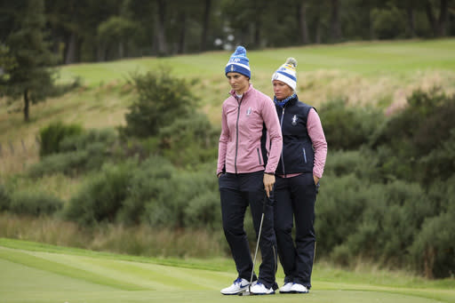 Anne Van Dam of Europe and Suzann Pettersen line up their putt on the 15th green during the Fourballs match against the US in the Solheim cup at Gleneagles, Auchterarder, Scotland, Saturday, Sept. 14, 2019. (AP Photo/Peter Morrison)