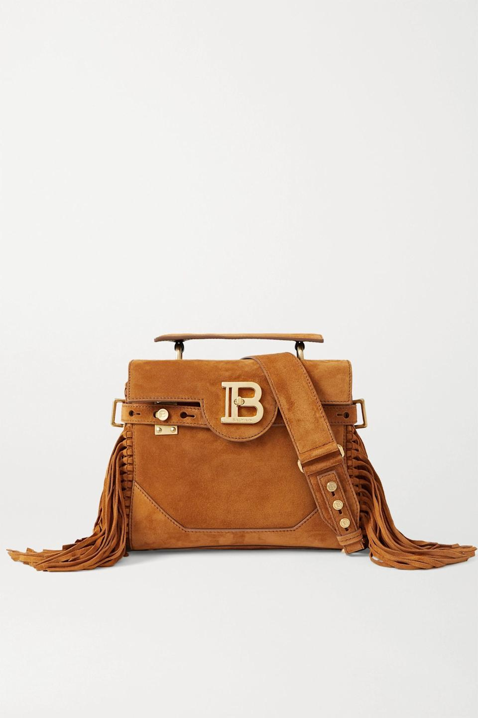 """<p><strong>Balmain</strong></p><p>net-a-porter.com</p><p><strong>$2195.00</strong></p><p><a href=""""https://click.linksynergy.com/deeplink?id=6Km1lFswsiY&mid=24449&murl=https%3A%2F%2Fwww.net-a-porter.com%2Fen-us%2Fshop%2Fproduct%2Fbalmain%2Fb-buzz-19-fringed-suede-shoulder-bag%2F1287171"""" rel=""""nofollow noopener"""" target=""""_blank"""" data-ylk=""""slk:Shop Now"""" class=""""link rapid-noclick-resp"""">Shop Now</a></p><p>This bag is the epitome of the return of '70s fashion. Everything from the fun fringe, suede fabric, and gold hardware will set you up for a breezy year ahead. </p>"""