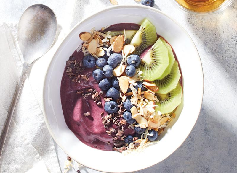 acai bowl with blueberries and kiwi in white bowl with spoon