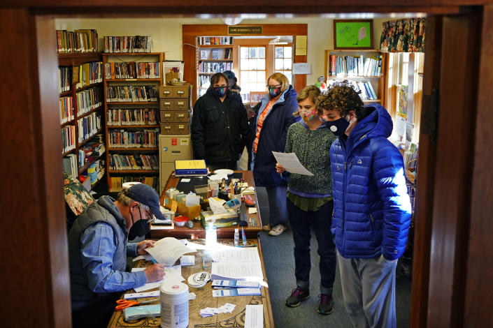 """John Zavodny, president of the Maine Seacoast Mission, left, registers residents for COVID-19 vaccinations in a library on the island of Islesford, Maine, Friday, March 19, 2021. """"Life on the islands is remote. And it's isolated. And I think that isolation is both the attraction but the heart of the challenge,"""" said Zavodny said. (AP Photo/Robert F. Bukaty)"""