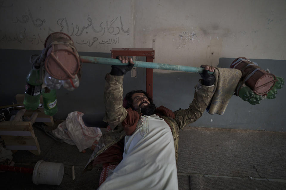 A Taliban fighter lifts a makeshift weight left behind by former prisoners at an empty area of the Pul-e-Charkhi prison in Kabul, Afghanistan, Monday, Sept. 13, 2021. Pul-e-Charkhi was previously the main government prison for holding captured Taliban and was long notorious for abuses, poor conditions and severe overcrowding with thousands of prisoners. Now after their takeover of the country, the Taliban control it and are getting it back up and running, current holding around 60 people, mainly drug addicts and accused criminals. (AP Photo/Felipe Dana)