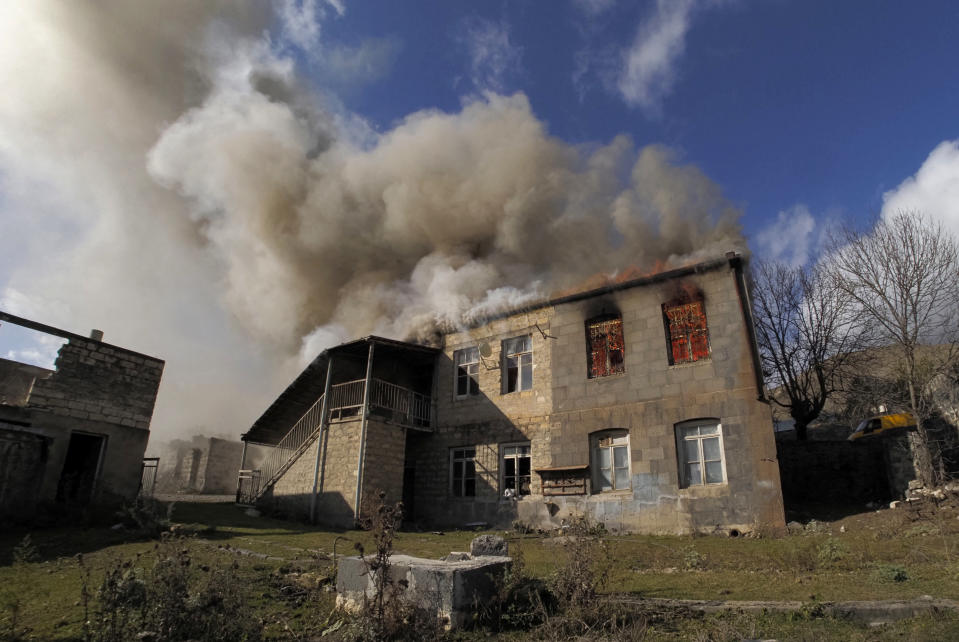 Smoke rises from a burning house in an area once occupied by Armenian forces but soon to be turned over to Azerbaijan, in Karvachar, the separatist region of Nagorno-Karabakh, on Friday, Nov. 13, 2020. Under an agreement ending weeks of intense fighting over the Nagorno-Karabakh region, some Armenian-held territories adjacent to the region are passing to Azerbaijan. (AP Photo/Dmitry Lovetsky)